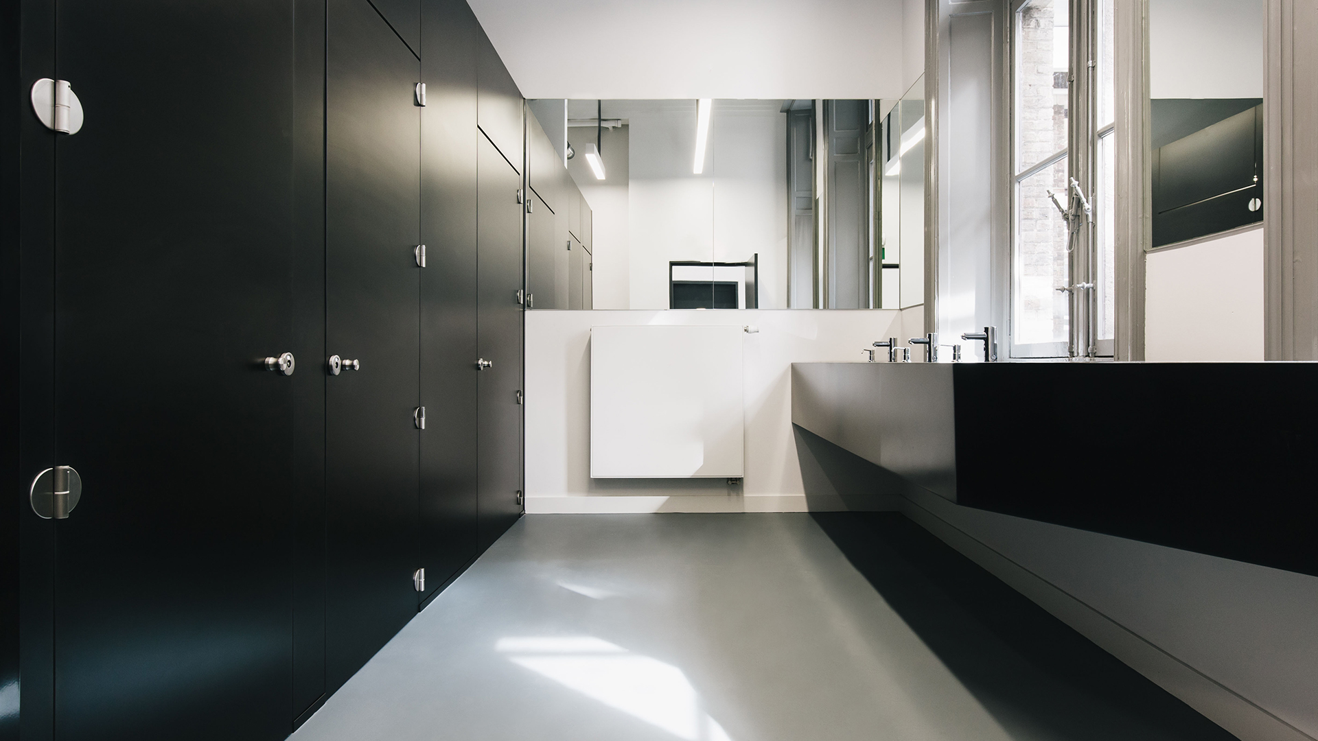 White bathroom with black partitions